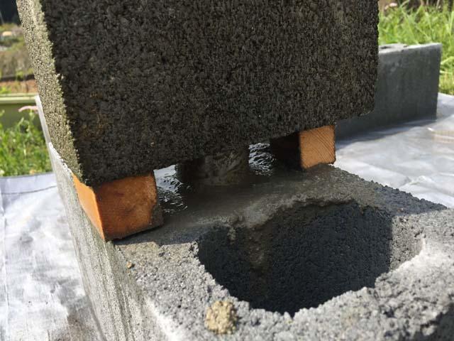 重量ブロックに単管パイプを入れてモルタルで固定する
